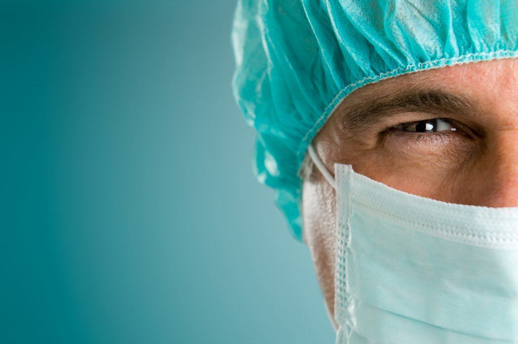 Mature male surgeon gazing and looking at camera at hospital, close up shot